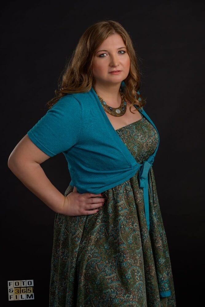 Fotografie facuta la o sedinta foto glamour, reprezentand o tanara blonda cu rochie colorata verde cu albastru, pe fundal negru