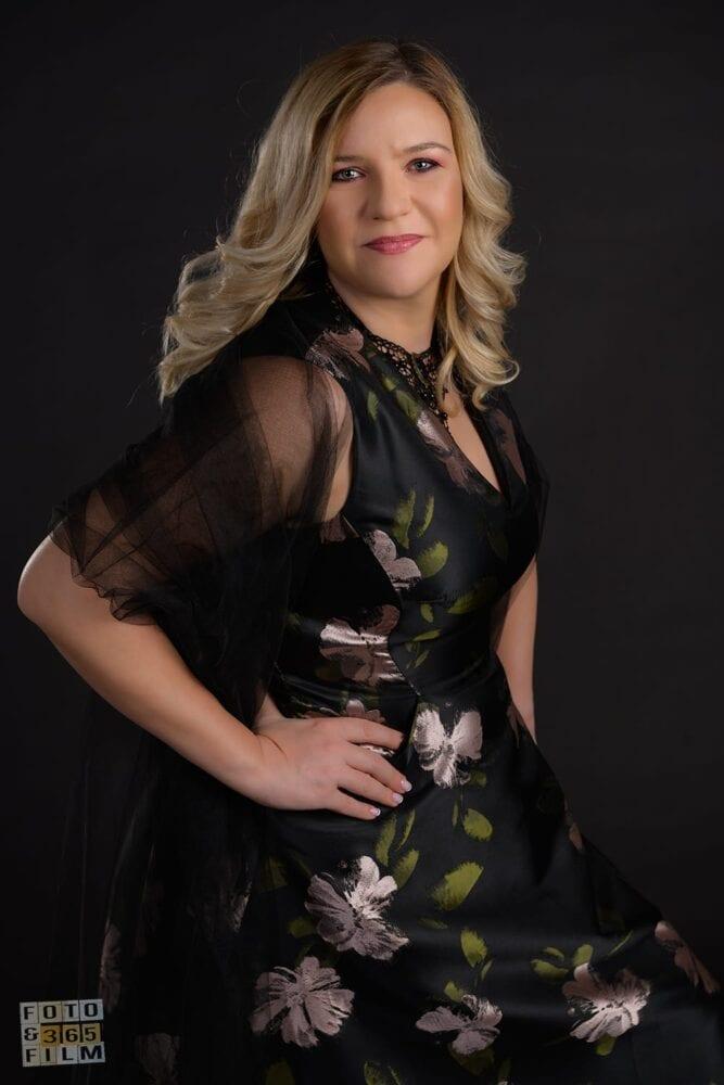 Fotografie facuta la o sedinta foto glamour, reprezentand o tanara doamna blonda cu rochie neagra si imprimeu verde cu argintiu, pe fundal negru